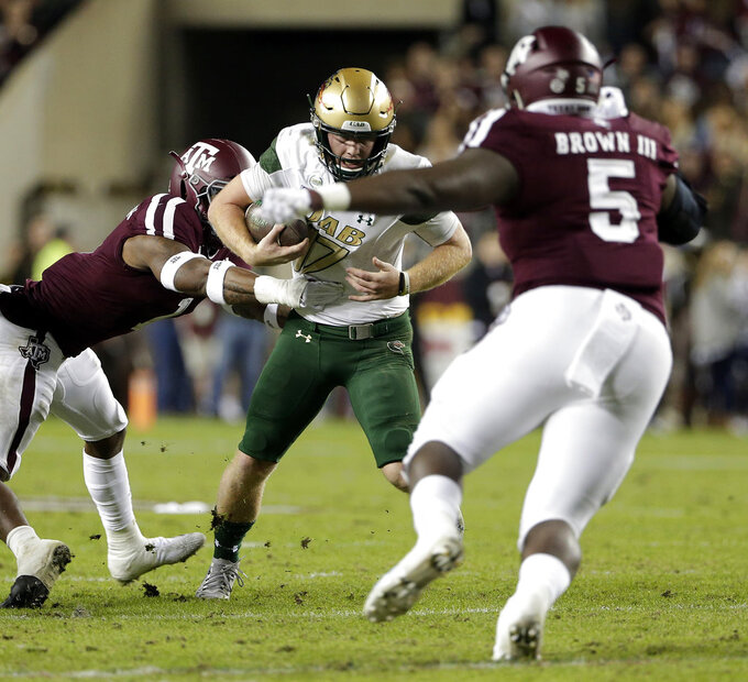 UAB quarterback Tyler Johnston III (17) is caught on a keeper play between Texas A&M linebacker Buddy Johnson, left, and defensive lineman Bobby Brown III, right, during the first half of an NCAA college football game Saturday, Nov. 17, 2018, in College Station, Texas. (AP Photo/Michael Wyke)
