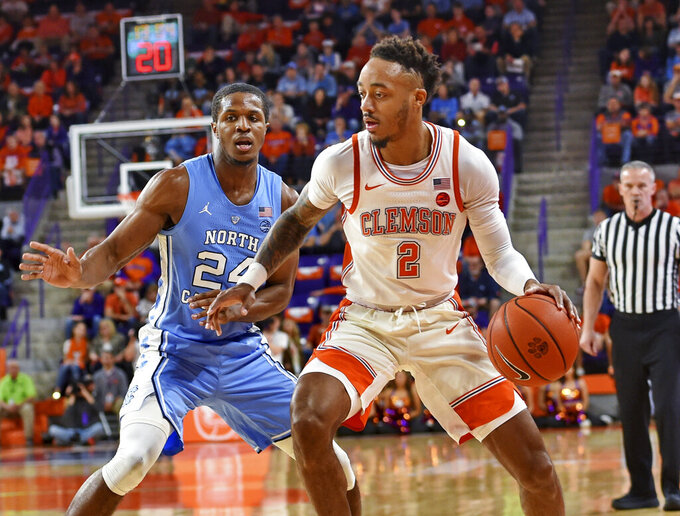 Clemson's Marcquise Reed works the baseline while defended by North Carolina's Kenny Williams during the first half of an NCAA college basketball game Saturday, March 2, 2019, in Clemson, S.C. (AP Photo/Richard Shiro)