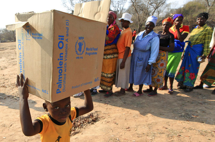 FILE - In this Sept. 9, 2015 file photo, a child carries a parcel from the United Nations World Food Program (WFP) in Mwenezi, Zimbabwe. The WFP has won the 2020 Nobel Peace Prize for its efforts to combat hunger and food insecurity around the globe. The announcement was made Friday Oct. 9, 2020 in Oslo by Berit Reiss-Andersen, the chair of the Nobel Committee. (AP Photo/Tsvangirayi Mukwazhi, File)