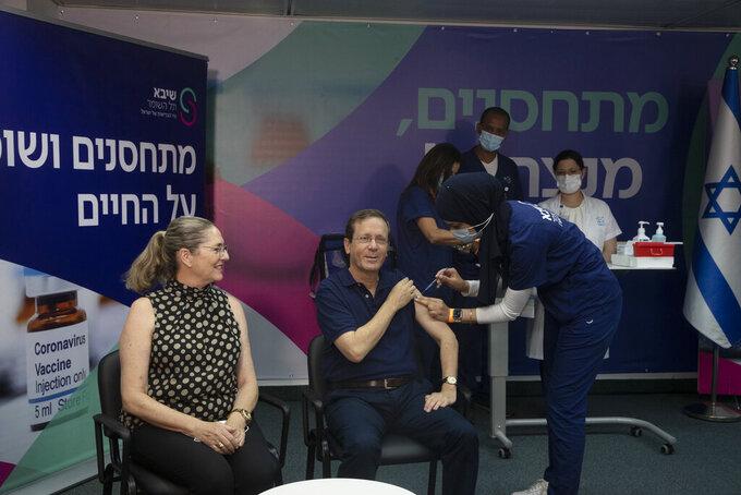 Israeli President Isaac Herzog receives a third coronavirus vaccine injection while his wife, Michal, left, reacts, at the Sheba Medical Center in Ramat Gan, Israel, Friday, July 30, 2021. (AP Photo/Maya Alleruzzo, Pool)
