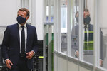 French President Emmanuel Macron, center, wearing a protective face mask, as he visits a Valeo manufacturer plant, in Etaples, , northern France, Tuesday May 26, 2020. France's government is injecting more than 8 billion euros ($8.8 billion) to save the country's car industry from huge losses wrought by virus lockdowns, and wants to use the crisis to make France the No. 1 producer of electric vehicles in Europe. (Ludovic Marin, Pool via AP)