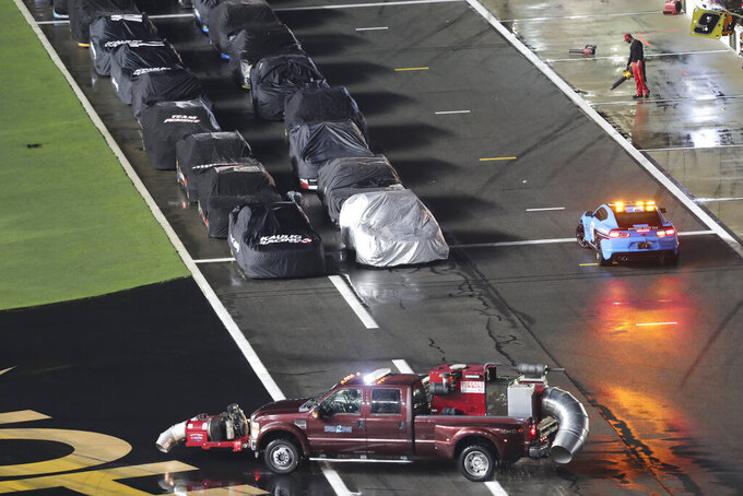 Cars line up on pit road near the pace car as a vehicle is used to dry the track, at the NASCAR Xfinity Series auto race at Daytona International Speedway, Friday, Aug. 27, 2021, in Daytona Beach, Fla. (AP Photo/David Graham)