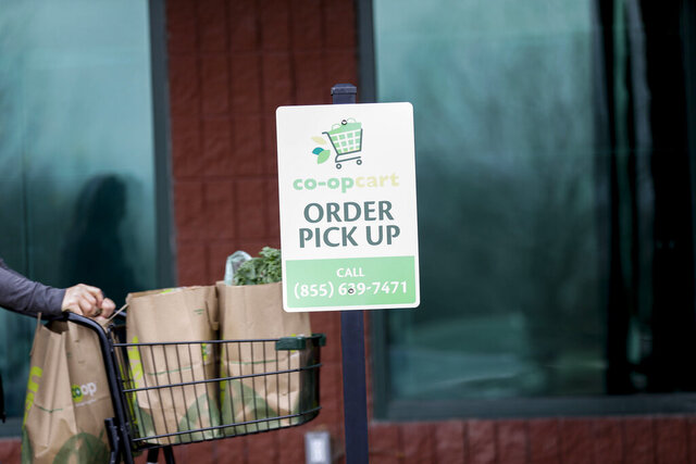 FILE - In this March 20, 2020 file photo, an order pickup station is seen at New Pioneer Co-Op in Coralville, Iowa. For many Americans, shopping for groceries online instead of at the store is becoming the new normal in the pandemic. But this method of stocking up could have an impact on your budget.   (Rebecca F. Miller/The Gazette via AP, File)