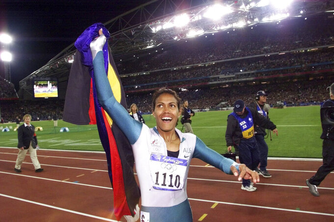 FILE - In this Sept. 25, 2000, file photo, Australia's Cathy Freeman celebrates winning the women's 400 meter race at the Summer Olympics at Olympic Stadium in Sydney. Freeman ignited the Olympic flame to open the Sydney 2000 Games and returned 10 nights later to win a gold medal in the 400 meters that had been a long time in waiting for country. She was the first Aboriginal person from Australia to win an individual Olympic gold. And she celebrated in a bare-foot victory lap with an Australian flag and the red, black and yellow Australian Aboriginal flag together in her hand. (AP Photo/Thomas Kienzle, File)