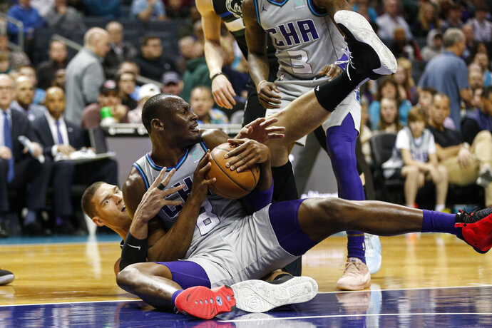Charlotte Hornets center Bismack Biyombo, front, battles Milwaukee Bucks center Brook Lopez for the ball in the second half of an NBA basketball game in Charlotte, N.C., Sunday, March 1, 2020. (AP Photo/Nell Redmond)