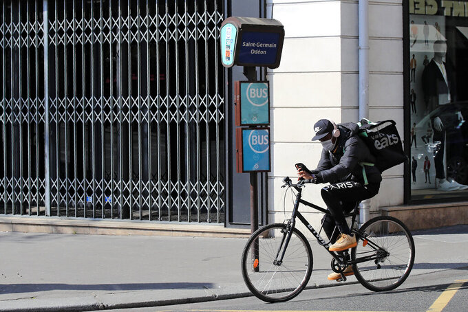 FILE - In this March 19, 2020 file photo, a food delivery service man rides his bike in Paris. Some 19 meal delivery companies in France including Uber Eats and Deliveroo have pledged to the French government to reduce their operational waste. With the pandemic-forced closure of restaurants, there has been a boom in home food delivery -- generating more waste that ever before. (AP Photo/Michel Euler, File)