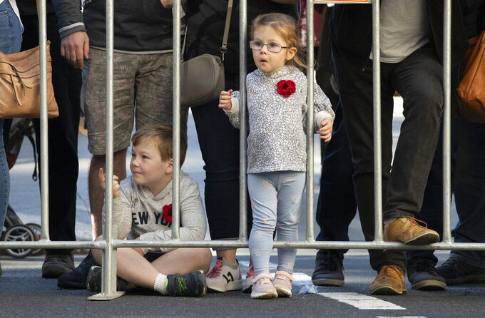 Children watch as veterans march in the Anzac Day parade in Sydney, Australia, Sunday, April 25, 2021. Australians and New Zealanders paid tribute to their war dead Sunday as both nations prepared to withdraw from their longest war in Afghanistan. (AP Photo/Mark Baker)