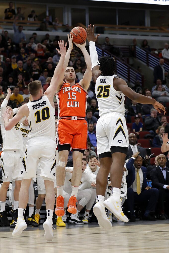 Illinois's Giorgi Bezhanishvili (15) takes a shot against Iowa's Joe Wieskamp (10) and Tyler Cook (25) during the first half of an NCAA college basketball game in the second round of the Big Ten Conference tournament, Thursday, March 14, 2019, in Chicago. (AP Photo/Nam Y. Huh)