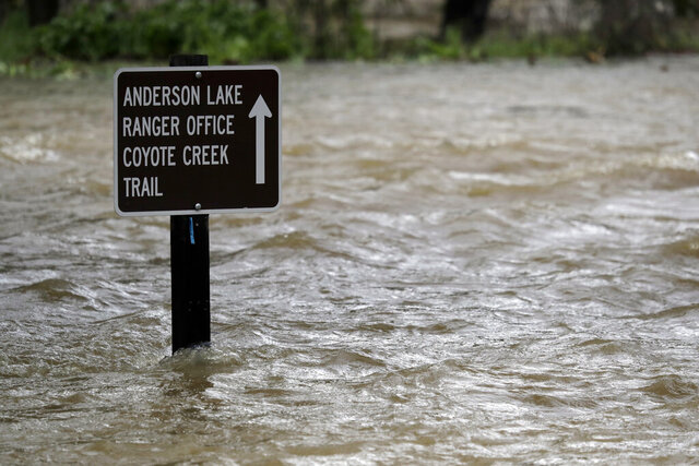 FILE - In this Feb. 21, 2017 file photo a sign is submerged in the water from Coyote Creek in Morgan Hill, Calif. U.S. officials are worried that an earthquake could collapse a big dam near Silicon Valley. They ordered its reservoir to be completely drained by October, 2020, due to concerns that the dam could send floodwaters into communities. Retrofit plans have been in the works for years and the dam's water level has been kept at a maximum of 74% since 2009. As of Monday, Feb. 24, 2020, the reservoir was just 29% full. (AP Photo/Marcio Jose Sanchez, File)