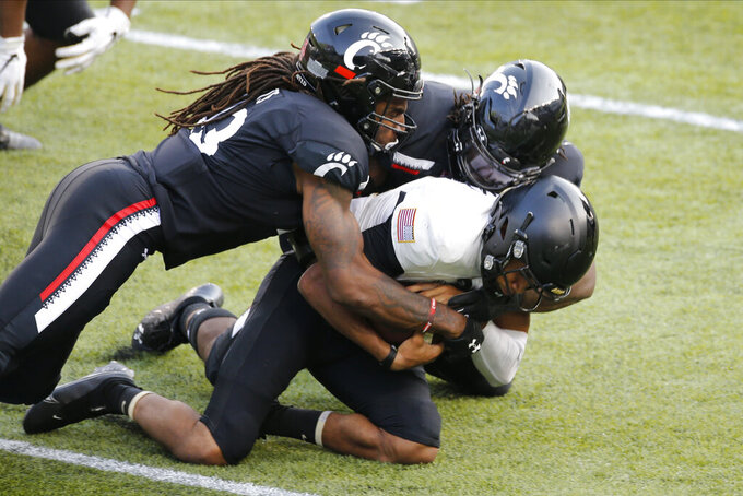Cincinnati defensive end Michael Pitts, left, and defensive lineman Curtis Brooks, center, sack Army quarterback Christian Anderson during the second half of an NCAA college football game Saturday, Sept. 26, 2020, in Cincinnati, Ohio. Cincinnati beat Army 24-10. (AP Photo/Jay LaPrete)