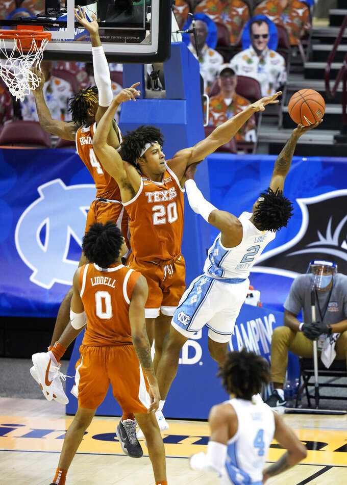 Texas forward Jericho Sims (20) blocks the shot North Carolina guard Caleb Love (2) as Texas forward Gerald Liddell (0) looks for the rebound 104in the first half of an NCAA college basketball game for the championship of the Maui Invitational, Wednesday, Dec. 2, 2020, in Asheville, N.C. (AP Photo/Kathy Kmonicek)