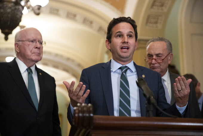 Sen. Patrick Leahy, D-Vt., left, and Senate Minority Leader Chuck Schumer of N.Y., right, listen as Sen. Brian Schatz, D-Hawaii, speaks about the coronavirus, Tuesday, March 3, 2020 in Washington. (AP Photo/Alex Brandon)