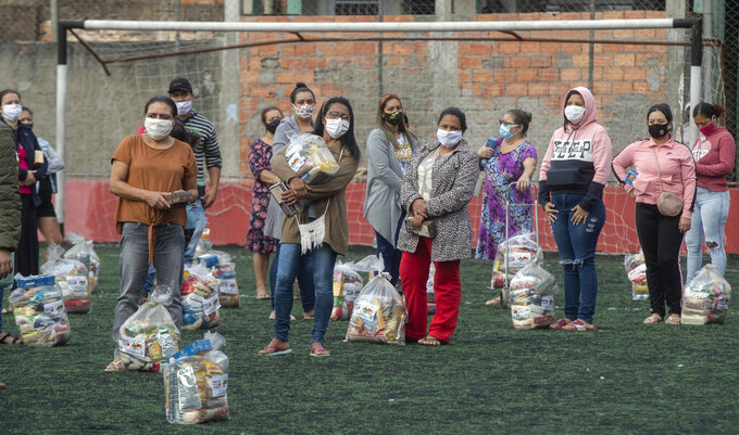 """Residents socially distance on a soccer field as they stand with bags of food donated by the local NGO """"G10 Favelas,"""" amid the COVID-19 pandemic in the Capao Redondo area of Sao Paulo, Brazil, Monday, April 26, 2021. (AP Photo/Andre Penner)"""