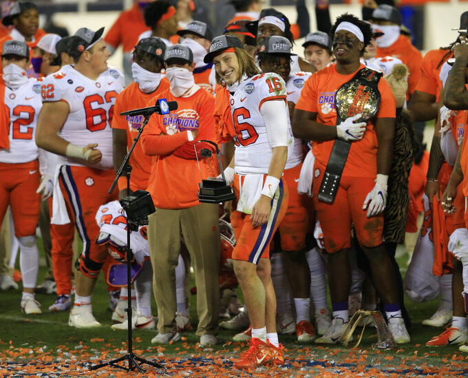 Clemson quarterback Trevor Lawrence (16) speaks to the media after being awarded the MVP trophy following the Tigers' 34-10 victory over Notre Dame in the Atlantic Coast Conference championship NCAA college football game, Saturday, Dec. 19, 2020, in Charlotte, N.C. (AP Photo/Brian Blanco)