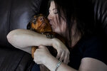Double lung transplant recipient Kari Wegg kisses her dachshund, Maisie, in her home in Westfield, Ind., Monday, March 22, 2021. The Indiana nurse came down with COVID-19 in the summer of 2020; her condition spiraled downward, and her life was saved only by grace of a double lung transplant. The road to normal is a long one, but she's bolstered by the love and support of her husband and sons, and by her own indomitable spirit. (AP Photo/Charles Rex Arbogast)