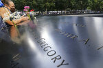A mourner prays over the inscribed name of the deceased Emilio Pete Ortiz at the National September 11 Memorial and Museum, Friday, Sept. 11, 2020, in New York. (AP Photo/John Minchillo)