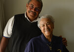 In this May 9, 2014 photo Jim Greenwood and his 101-year-old mother Marie Louise Greenwood pose for a portrait at her Denver home.  Greenwood, a pioneering Denver teacher who devoted decades to fighting segregation in city institutions, has died. She was 106. Greenwood died on Friday, Nov. 15, 2019 at her Denver residence, said Elder Shane Stringfellow of Caldwell Kirk Mortuary. (Cyrus McCrimmon/The Denver Post via AP)