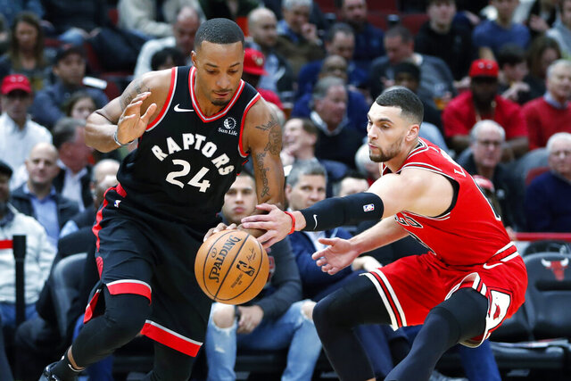 Toronto Raptors' Norman Powell (24) drives to the basket past Chicago Bulls' Zach LaVine during the first half of an NBA basketball game Monday, Dec. 9, 2019, in Chicago. (AP Photo/Charles Rex Arbogast)