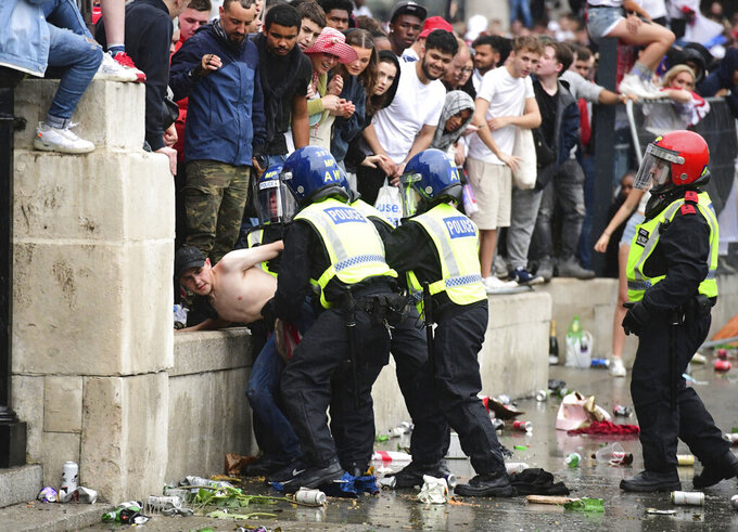 Police officers detain a fan gather in front of the National Gallery, in Trafalgar Square, London, Sunday July 11, 2021, ahead of the Euro 2020 soccer championship final match between England and Italy at Wembley Stadium. (Ian West/PA via AP)