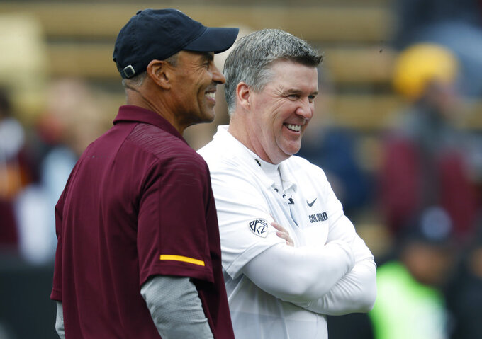 Arizona State head coach Herm Edwards, front, jokes with Colorado head coach Mike MacIntyre before an NCAA college football game Saturday, Oct. 6, 2018, in Boulder, Colo. (AP Photo/David Zalubowski)