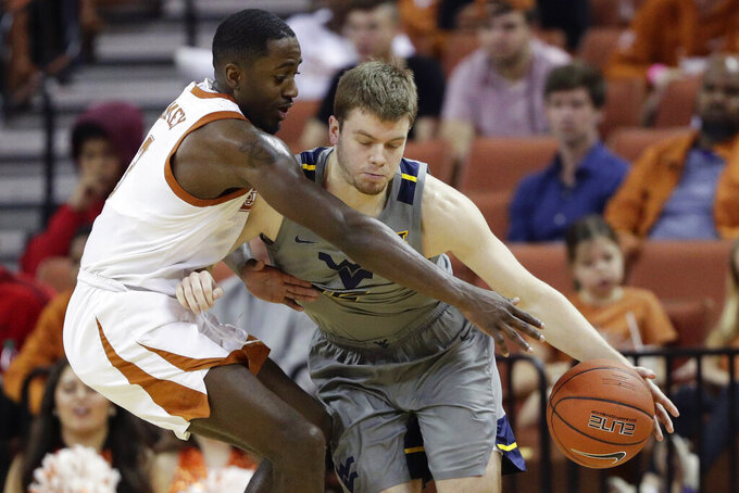 West Virginia guard Sean McNeil, right, is pressured by Texas guard Courtney Ramey, left, during the second half of an NCAA college basketball game, Monday, Feb. 24, 2020, in Austin, Texas. (AP Photo/Eric Gay)