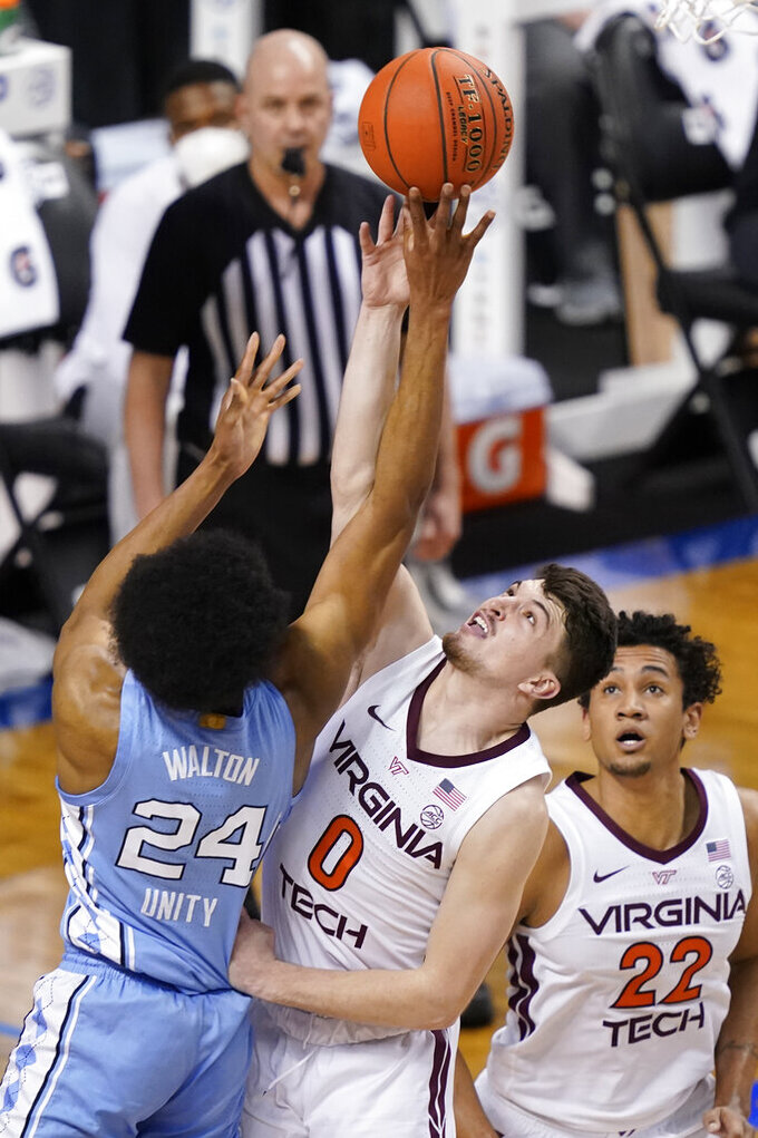North Carolina guard Kerwin Walton (24) goes up for a shot as Virginia Tech guard Hunter Cattoor (0) and forward Keve Aluma (22) defend during the first half of an NCAA college basketball game in the quarterfinals of the Atlantic Coast Conference men's tournament in Greensboro, N.C., Thursday, March 11, 2021. (AP Photo/Gerry Broome)