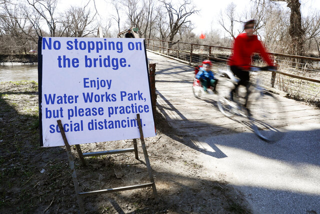 A cyclist passes a sign directing riders to practice social distancing on a bridge in Water Works Park, Monday, March 30, 2020, in Des Moines, Iowa. The new coronavirus causes mild or moderate symptoms for most people, but for some, especially older adults and people with existing health problems, it can cause more severe illness or death. (AP Photo/Charlie Neibergall)
