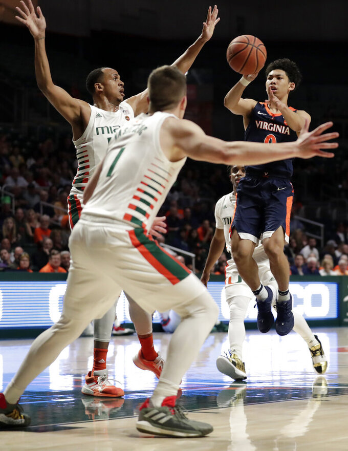 Virginia guard Kihei Clark, right, shoots as Miami center Rodney Miller Jr., center, and guard Dejan Vasiljevic (1) defend during the first half of an NCAA college basketball game, Wednesday, March 4, 2020, in Coral Gables, Fla. (AP Photo/Lynne Sladky)