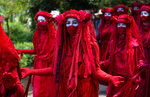 Activists in costume march during a demonstration around the meeting of the G7 in Falmouth, Cornwall, England, Saturday, June 12, 2021. Leaders of the G7 gather for a second day of meetings on Saturday, in which they will discuss COVID-19, climate, foreign policy and the economy. (AP Photo/Alberto Pezzali)