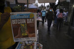 """A newspaper vendor shows the front page of a state-run newspaper carrying the headline """"Bitcoin Day"""" in San Salvador, El Salvador, Tuesday, Sept. 7, 2021. Starting Tuesday, all businesses will have to accept payments in Bitcoin, except those lacking the technology to do so, according to a law approved by the congress. (AP Photo/Salvador Melendez)"""