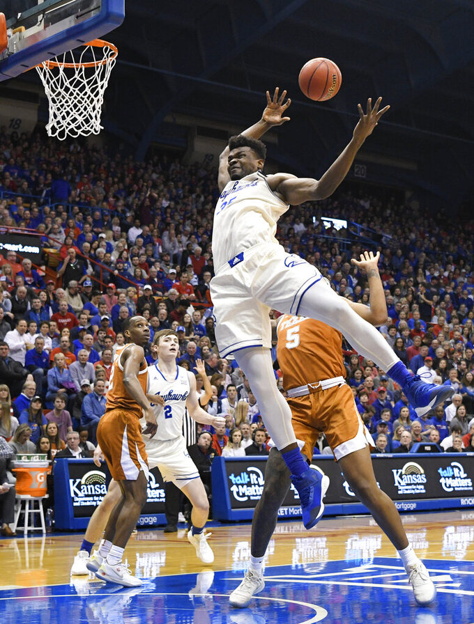 Kansas center Udoka Azubuike (35) is fouled by Texas forward Royce Hamm Jr. (5) going for a rebound during the first half of an NCAA college basketball game in Lawrence, Kan., Monday, Feb. 3, 2020. (AP Photo/Reed Hoffmann)
