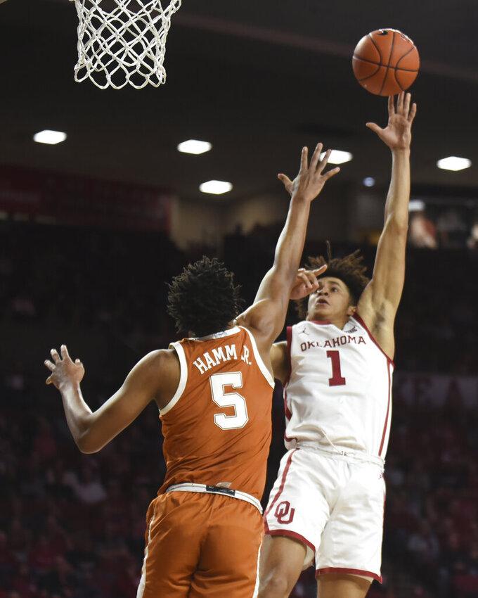 Oklahoma forward Jalen Hill (1) shoots over Texas forward Royce Hamm Jr. (5) during the first half of an NCAA college basketball game in Norman, Okla., Tuesday, March 3, 2020. (Kyle Phillips/The Norman Transcript via AP)