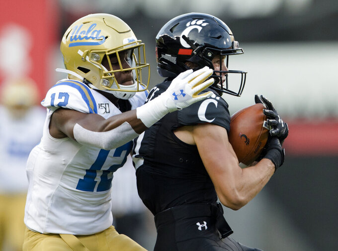 Cincinnati wide receiver Alec Pierce (12) catches a pass as UCLA defensive back Elijah Gates (12) moves in to make the tackle during the first half of an NCAA college football game Thursday, Aug. 29, 2019, in Cincinnati. (Albert Cesare/The Cincinnati Enquirer via AP)