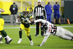 Green Bay Packers' Aaron Jones (33) runs past Atlanta Falcons' Dante Fowler Jr. (56) during the second half of an NFL football game, Monday, Oct. 5, 2020, in Green Bay, Wis. (AP Photo/Mike Roemer)