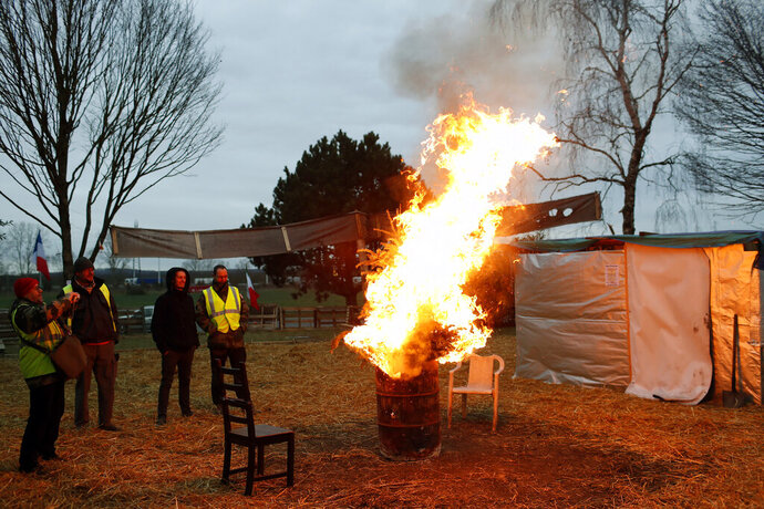 Protestors wearing yellow vests stand next to a fire in a makeshift camp on a roundabout near Senlis, north of Paris, Thursday, Jan. 10, 2019. With its makeshift grocery, camp beds and community spirit, the large central island about 60 kilometers north of Paris has been transformed over the past two months into an encampment where dozens of yellow vests protesters gather day in day out to organize their long-standing fight against the French government. (AP Photo/Thibault Camus)