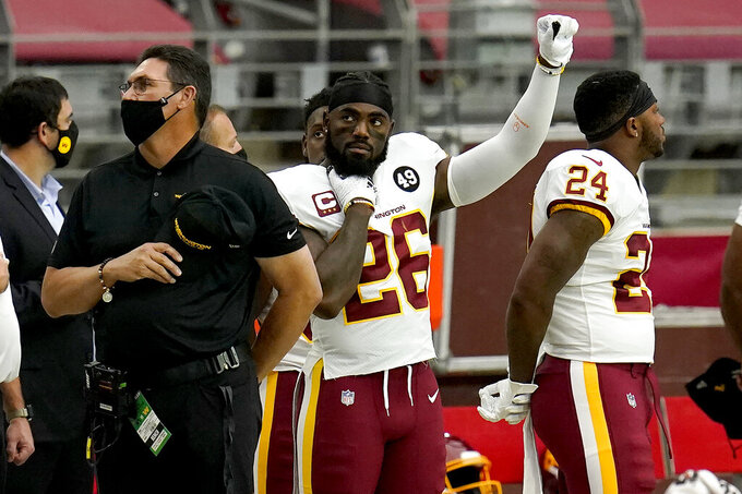 Washington Football Team head coach Ron Rivera and strong safety Landon Collins (26) stand during the national anthem prior to an NFL football game against the Arizona Cardinals, Sunday, Sept. 20, 2020, in Glendale, Ariz. (AP Photo/Ross D. Franklin)