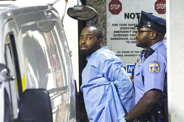 Police take shooting suspect, Maurice Hill, into custody after a standoff with police that wounded several police officers, in Philadelphia early Thursday, Aug. 15, 2019. The Philadelphia man charged with shooting six police officers during an hours-long standoff last summer, was held for trial Thursday, Aug. 13, 2020 on a third set of charges stemming from the incident. (Elizabeth Robertson/The Philadelphia Inquirer via AP)