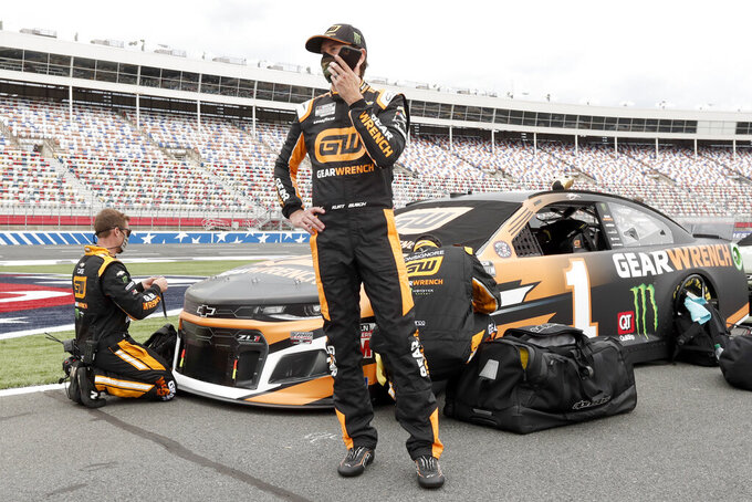 Kurt Busch talks on his phone before the start of the NASCAR Cup Series auto race at Charlotte Motor Speedway Sunday, May 24, 2020, in Concord, N.C. (AP Photo/Gerry Broome)