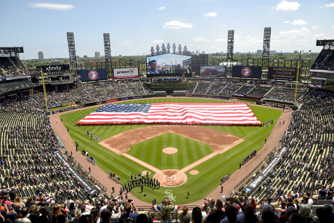 FILE - In this July 4, 2019, file photo, an American Flag is unfurled in the outfield during the playing of the National Anthem before the start a baseball game between the Chicago White Sox and the Detroit Tigers in Chicago. Thousands of fans of the Chicago Cubs and the Chicago White Sox will get to see their teams play in person this season, Mayor Lori Lightfoot announced on Monday, March 9, 2021. In a news release, Lightfoot said each team will be limited to 20% capacity. (AP Photo/Mark Black, File)