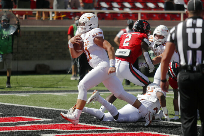 Texas quarterback Sam Ehlinger scores a touchdown during the first half of an NCAA college football game against Texas Tech, Saturday Sept. 26, 2020, in Lubbock, Texas. (AP Photo/Mark Rogers)