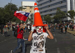 Anti-government protesters block streets in Santiago, Chile, Wednesday, Oct. 30, 2019. Chilean President Sebastián Pinera cancelled two major international summits after nearly two weeks of nationwide protests over economic inequality that have left at least 20 dead and damaged businesses and infrastructure around the country. (AP Photo/Esteban Felix)
