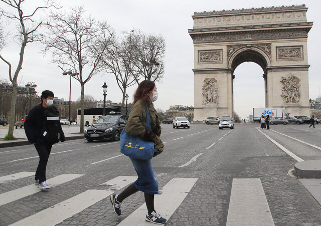 Tourist cross the Champs Elysees avenue in Paris, Monday, March 16, 2020. France's government announced Saturday closing restaurants, bars and other establishments to limit the spread of the new coronavirus. For most people, the new coronavirus causes only mild or moderate symptoms, such as fever and cough. For some, especially older adults and people with existing health problems, it can cause more severe illness, including pneumonia. (AP Photo/Michel Euler)