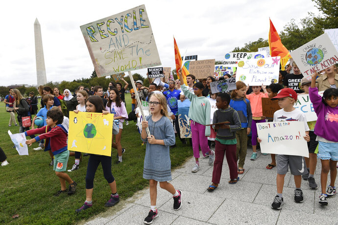 FILE - In this Friday, Sept. 13, 2019 file photo, young climate activists march with signs during a rally near the White House in Washington. At left is the Washington Monument. In late September 2019, there will be climate strikes, climate summits, climate debates, a dire climate science report, climate pledges by countries and businesses, promises of climate financial help and more between now and next Friday. There will even be a bit of climate poetry, film and music. (AP Photo/Susan Walsh)