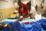 Nurses Valein Elda, left center, and Ricelin Chantale, tend to 14-year-old Miguelson Joseph at the Baptiste Mission Hospital in Kenscoff, just outside of Port-au-Prince, Haiti, Saturday, Feb. 15, 2020. Miguelson was injured when he jumped from a balcony at a branch of the Orphanage of the Church of Bible Understanding, trying to flee during a raid in which police were ordered to remove the children, after a fire swept through a nearby orphanage also run by the Pennsylvania-based nonprofit group, killing 15 children, officials said Friday. (AP Photo/Dieu Nalio Chery)