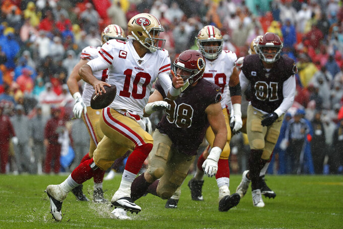 San Francisco 49ers quarterback Jimmy Garoppolo (10) looks for a receiver as he is pressured by Washington Redskins defensive end Matthew Ioannidis in the first half of an NFL football game, Sunday, Oct. 20, 2019, in Landover, Md. (AP Photo/Alex Brandon)