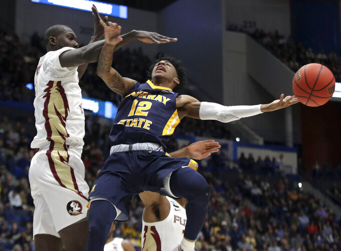 Murray State's Ja Morant (12) passes the ball under defensive pressure from Florida State's Christ Koumadje (21) during the first half of a second round men's college basketball game in the NCAA Tournament, Saturday, March 23, 2019, in Hartford, Conn. (AP Photo/Elise Amendola)