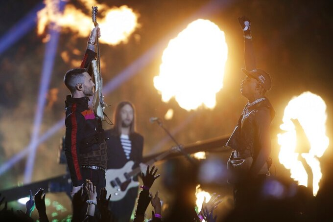 Adam Levine of Maroon 5, left, and Travis Scott salute each other during halftime of the NFL Super Bowl 53 football game between the Los Angeles Rams and the New England Patriots Sunday, Feb. 3, 2019, in Atlanta. (AP Photo/Matt Rourke)
