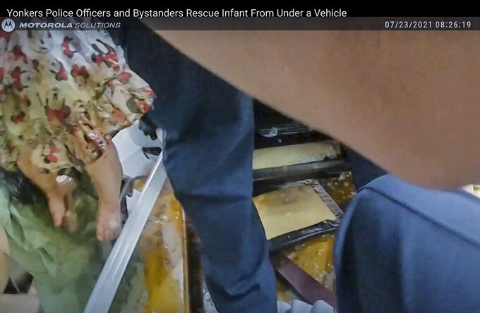 This image from a police bodycam video provided by Yonkers Police Department on Saturday, July 24, 2021, shows police and bystanders lifting a car to free a trapped baby, left, after a suspected drunken driver struck the child and her mother and plowed into a storefront in Yonkers. (Yonkers Police Department via AP)