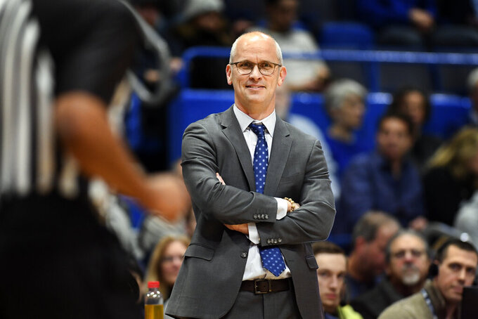 FILE - In this Dec. 29, 2019, file photo, Connecticut coach Dan Hurley smiles as he watches his team during the second half of an NCAA college basketball game against New Jersey Institute of Technology in Hartford, Conn. UConn, a charter member of the Big East Conference, is hoping its return to the league this season will help restore the program to a position as a perennial national title contender. Hurley acknowledged that the Big East is an easier sell to big-name recruits, especially in the Northeast. (AP Photo/Stephen Dunn, File)