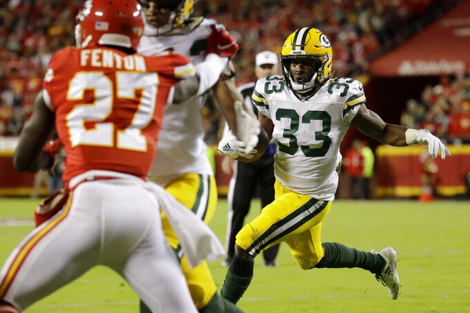 Green Bay Packers running back Aaron Jones (33) runs for a touchdown as Kansas City Chiefs cornerback Rashad Fenton (27) defends during the first half of an NFL football game in Kansas City, Mo., Sunday, Oct. 27, 2019. (AP Photo/Charlie Riedel)
